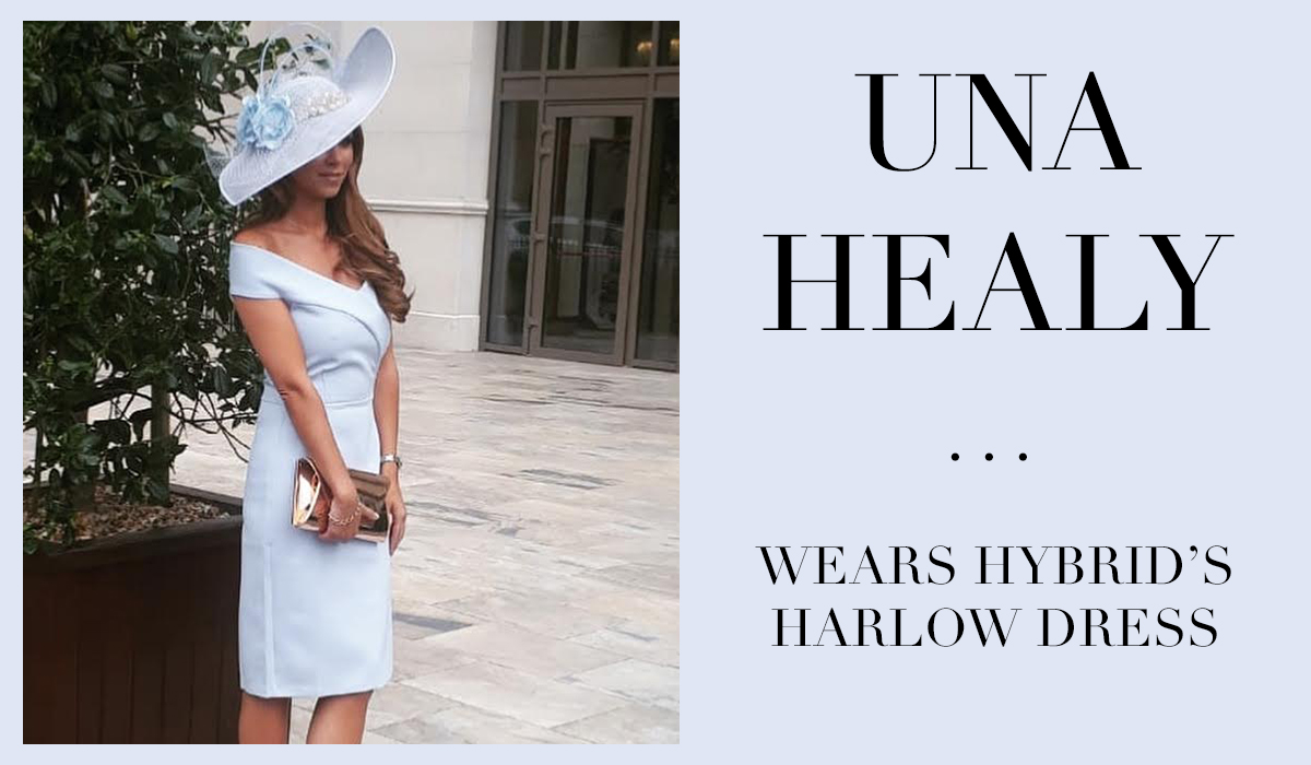 Celeb Una Healy wearing a hybrid baby blue dress wearing a had and holding a clutch bag while standing outside for photographers