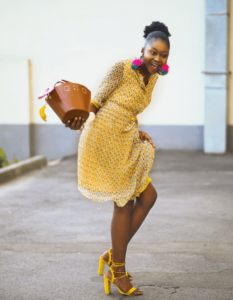 Woman wearing a yellow dress and heels and holding a bag