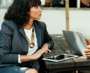 Woman wearing a suit and sitting with a laptop and iPad