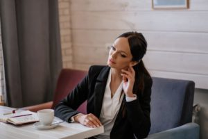 Woman wearing a suit and sitting with a cup of coffee and notebook