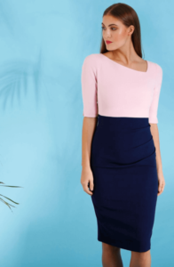 Woman wearing a pink and navy blue pencil dress by a blue background