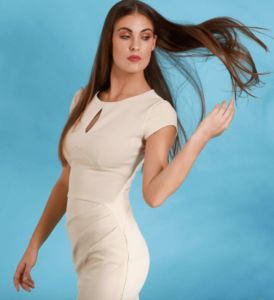 Woman wearing a cream or off-white wiggle dress and flicking her hair