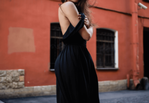 Woman wearing a long black dress near a building