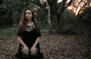 Woman wearing a lace black dress and sitting in a forest during sunset