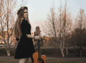 Woman wearing a black dress, floral headpiece and holding a guitar in a park