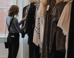 Woman looking through clothing rack of clothing and shopping for sustainable fashion