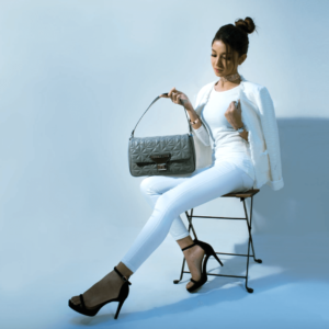 Woman wearing white jeans and blazer while sitting on chair with handbag