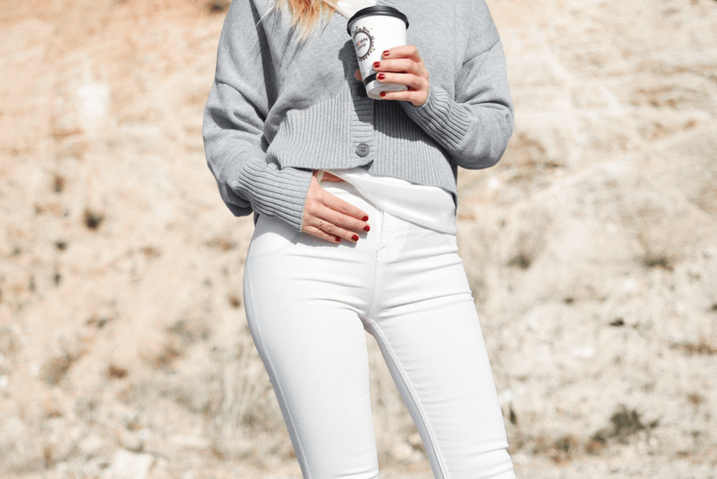 Lady wearing white jeans and cardigan while holding coffee cup