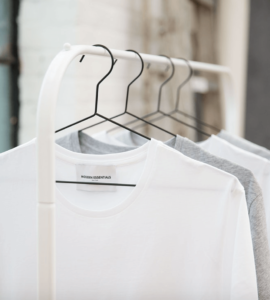 Capsule wardrobe of white clothing hanging on clothes hanger