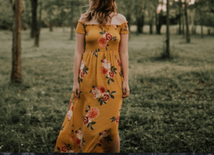 Lady wearing capsule wardrobe essential mustard maxi dress in field