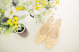Yellow ankle strap flat shoes with yellow plant in the background