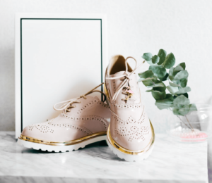 Pink, brogue shoes with plant and shoe box on marble table