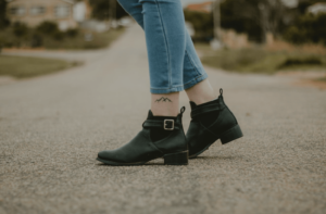 Lady wearing black ankle boot shoes with jeans