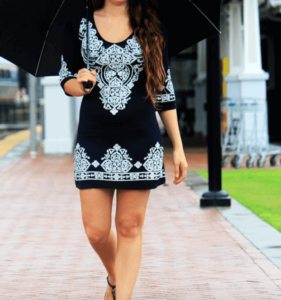 Woman wearing a black bodycon dress with white detail and holding an umbrella
