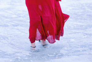 Woman wearing red dress and heels in a puddle in the rain