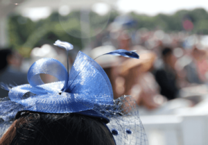 Woman wearing a blue headpiece at a day at the races