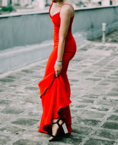 Woman wearing a formal red dress with heels that is suitable for a day at the races