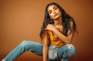 Woman wearing yellow top and jeans and posing on brown background