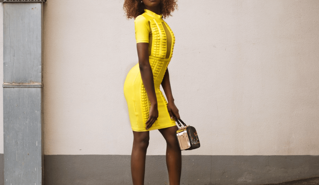 Woman wearing a bright yellow sheath dress and holding a purse