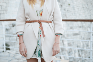 Woman wearing dress with oversized white cardigan and belt for transition dressing
