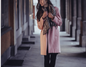 Woman transitional dressing for fall with a pink coat and scarf