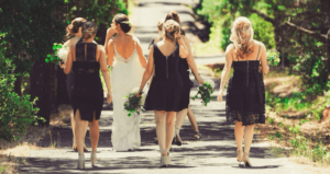 Bride on her wedding day walking with bridesmaids and wedding guests wearing black dresses