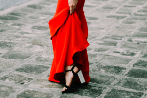 Woman wearing red dress with slit and block heels on tips to avoid wardrobe malfunctions