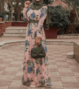 Woman wearing pink floral modest dress with a purse