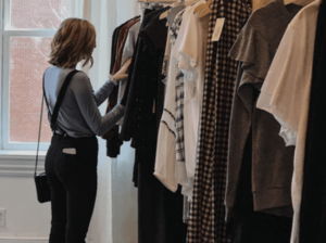 Woman looking through clothes on a clothing rack in a shop