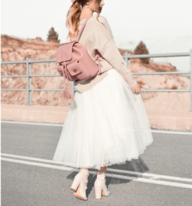 Woman wearing white, net skirt and pink backpack with chunky heels