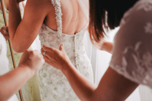 Bridesmaid helping bride put on her dressing gown