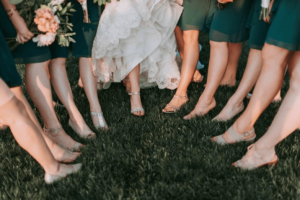 A bridal party of bridesmaids and the bride showing off their shoes