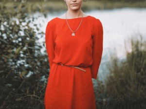 Woman wearing red dress with belt to accentuate her body shape and standing by a lake