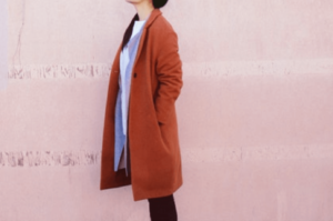Woman wearing a modest jacket and standing near a pink wall