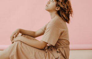 Woman wearing modest jumpsuit and sitting near pink wall