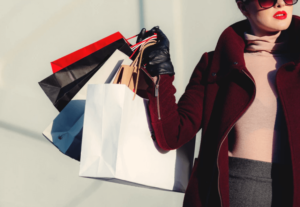 Woman wearing red lipstick and coat while holding lots of shopping bags
