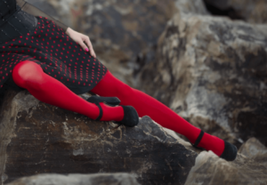 Lady wearing bright red tights with black dress and sitting on rocks