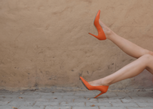 Woman wearing a pair of bright orange heel shoes