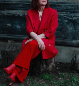 Woman wearing red suit and sitting on stairs