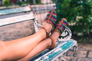 Woman wearing colorful sandals with her feet up on a bench