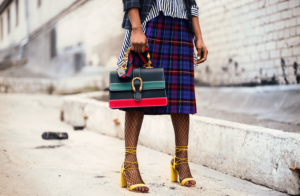 Woman wearing smart, stylish clothes with a checked shirt while holding a handbag and wearing yellow heels on her feer
