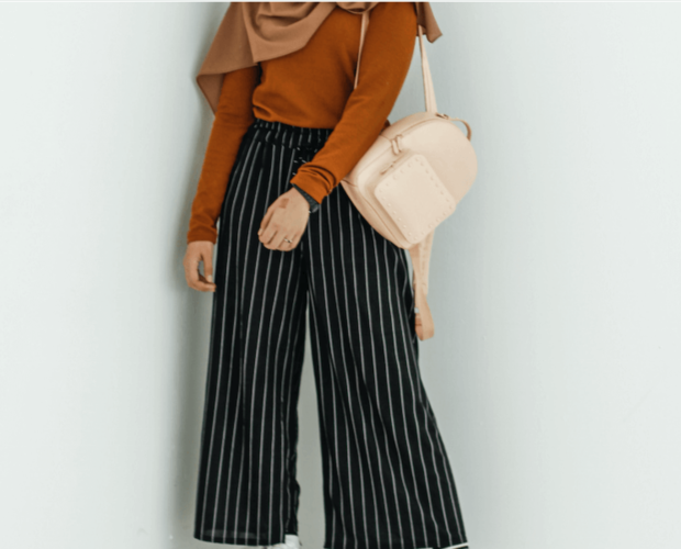 Woman wearing modest fashion clothes with stripy trousers and holding pink backpack