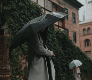 Woman wearing a formal coat and holding an umbrella in the rain