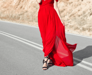 Woman wearing a long, elegant dress with heels on a road