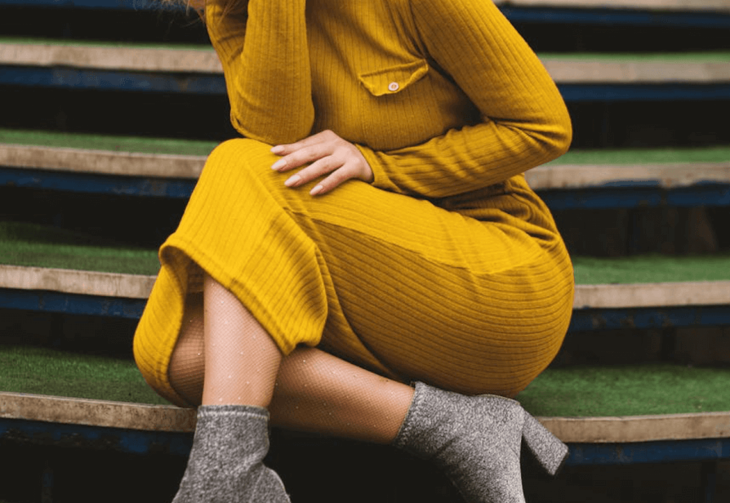Woman wearing yellow bodycon dress with grey shoes and sitting on stairs