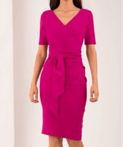 Woman wearing a pink dress with a wrap around the waist that can be worn to work