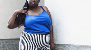 A plus size woman wearing a blue top and stripy trousers