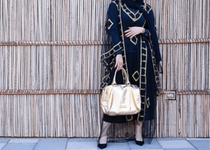 Woman wearing a modest black dress with a gold bag