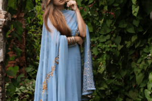 Woman wearing a blue dress with bangles and a shawl