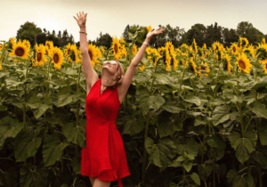 A woman wearing a strapless red wrap dress in a sunflower field